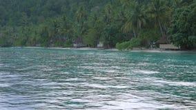 Chuva tropical sobre as cabanas de bambu do homestay na praia, Gam Island, Raja Ampat, Papua ocidental, Indonésia vídeos de arquivo