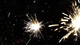 Chuveirinho do fogo de artifício que queima-se com os flocos de neve da dança contra o fundo preto do céu noturno Blizzard do tem vídeos de arquivo