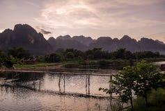 Chwalebnie zmierzch Laos nad górami które dominują Vang Vieng przegapia Nam Pieśniową rzekę i drewnianego most, obrazy stock