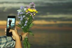 Chwyta? pi?knego kwiatu bukiet w r?ce inn? r?k? z czarnym m?drze telefonem, multitasking r?ki Rozmyci niebo kolory i fotografia royalty free