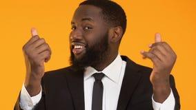 Chytry afroamerykański mężczyzny nacierania palec, pytać dla pieniądze, żądający łapówkę zbiory