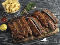 Ciąć piec na grillu wieprzowina ziobro z kumberlandem na desce, francuscy dłoniaki, pikantność, drewniany tło zdjęcia stock
