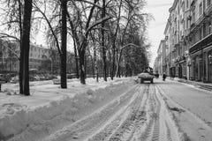 Ciągnik usuwa białego śnieg na miasto ulicie w zimie czarny white zdjęcia royalty free