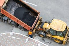 Ciężka przemysłowa usyp ciężarówka rozładowywa gorącego asfalt Miasta budowa drogi i odnowienia miejsce zdjęcia royalty free
