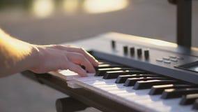 Ciérrela para arriba juega el sintetizador en la puesta del sol FHD metrajes