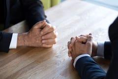 Ciérrese de hombres de negocios se incorporan con las manos apretadas tomando la decisión imagen de archivo
