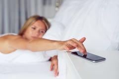 Ciérrese encima de alarma femenina el dormitar de la mano en el teléfono móvil foto de archivo