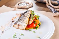 Ciérrese encima de asar a la parrilla el filete de pescados con la almohada vegetal servida en la placa blanca Porción del restau Foto de archivo