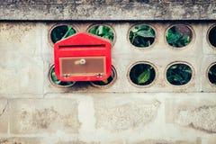Ciérrese encima de buzón rojo en la pared del cemento Imagenes de archivo