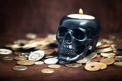 Ciérrese encima de candelero del cráneo con las monedas Imagenes de archivo
