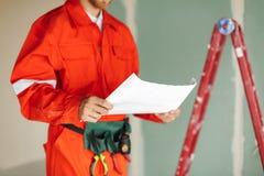 ffe862ef894 Ciérrese encima de capataz en ropa de trabajo anaranjada y holdi amarillo  del casco de protección