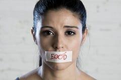Ciérrese encima de cara de la mujer latina triste hermosa joven con la boca sellada en la cinta del palillo con el texto ninguna  Imagen de archivo