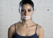 Ciérrese encima de cara de la mujer latina triste hermosa joven con la boca sellada en la cinta del palillo con el texto ninguna  Fotografía de archivo