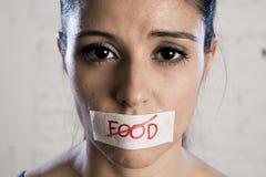 Ciérrese encima de cara de la mujer latina triste hermosa joven con la boca sellada en la cinta del palillo con el texto ninguna  Imagen de archivo libre de regalías