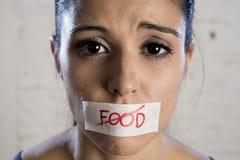 Ciérrese encima de cara de la mujer latina triste hermosa joven con la boca sellada en la cinta del palillo con el texto ninguna  Foto de archivo libre de regalías