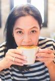 Ciérrese encima de cara del café caliente del capuchino del sorbo asiático de la mujer en el café s Imagen de archivo libre de regalías