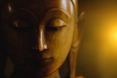 Ciérrese encima de cara en la estatua de la cabeza de Buda con efecto luminoso Fotos de archivo