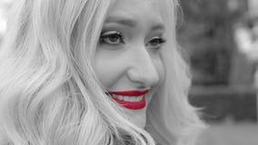 Ciérrese encima de cara La muchacha rubia joven con el pelo rizado está sonriendo almacen de video