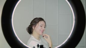 Ciérrese encima de cara morena atractiva de la mujer con el pelo soplado aire, mirando la cámara Ring Light Beauty metrajes