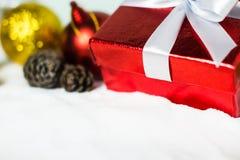 Ciérrese encima de cinta blanca roja de la caja de regalo con la bola y el pino de la Navidad Fotos de archivo libres de regalías