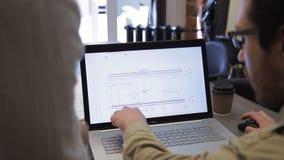 Ciérrese encima de dibujos de estudio de las imágenes en el ordenador portátil de la reunión dentro de la oficina almacen de video