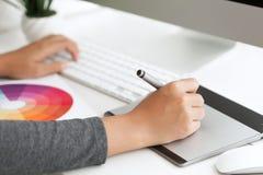 Ciérrese encima de diseño gráfico usando la tableta digital de la pluma en workspa del escritorio Foto de archivo