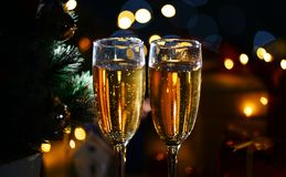 Ciérrese encima de dos vidrios de Champagne Beside Christmas Tree Oscuridad cerca fotografía de archivo