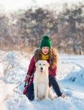 Ciérrese encima de dueño feliz de la mujer y del perro blanco del golden retriever en día de invierno Fotos de archivo