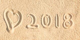 Ciérrese encima de escrito 2018 en la arena de una playa con un corazón Fotos de archivo