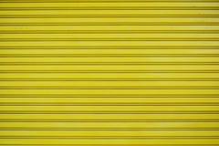 Ciérrese encima de fondo de la textura de la puerta de la diapositiva de la hoja de metal amarillo Foto de archivo libre de regalías