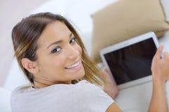 Ciérrese encima de hembra con la tableta que miente en el sofá Imagenes de archivo