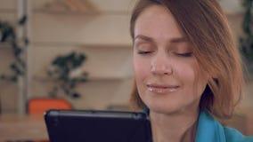 Ciérrese encima de hembra de la cara del júbilo con el dispositivo digital almacen de video