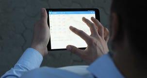 Ciérrese encima de hombre de negocios usando su Internet de la tecnología de la pantalla táctil de las comunicaciones empresarial almacen de video