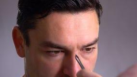 Ciérrese encima de hombre hermoso delante de un espejo cuida para su cara saca exceso de pelo el suyo Crema, expresión metrajes