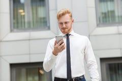 Ciérrese encima de hombre de negocios adulto joven del jengibre trabajo en el teléfono móvil y mirada del teléfono elegante de la Foto de archivo libre de regalías