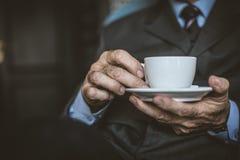 Ciérrese encima de hombre de negocios mayor de la imagen con una taza de café Foco encendido Fotos de archivo