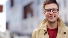 Ciérrese encima de hombre sonriente en lentes al aire libre almacen de metraje de vídeo