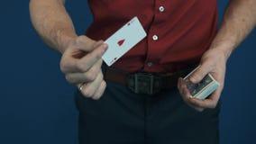 Ciérrese encima de ilusionista en la camisa roja que muestra focos de la magia de los naipes almacen de video