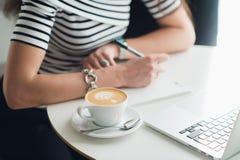 Ciérrese encima de imagen de una taza de capuchino con un modelo y las manos que escriben en un cuaderno Mujer que se sienta en u fotos de archivo libres de regalías