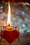 Ciérrese encima de imagen en la vela ardiente hecha de cera de abejas en el candelero de cristal con el corazón rojo Foto de archivo