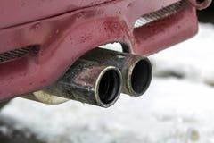 Ciérrese encima de imagen de un tubo de escape dual del coche Emisión del gas de monóxido de carbono venenoso en la atmósfera, co foto de archivo libre de regalías