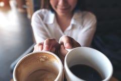Ciérrese encima de imagen de una mujer que sostiene dos tazas del café con leche Imagen de archivo libre de regalías