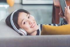 Ciérrese encima de juego de la música del adolescente que escucha de la muchacha del auricular asiático del desgaste Imagenes de archivo