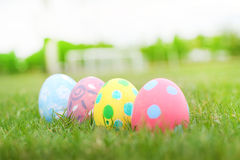 Ciérrese encima de línea en colores pastel de cuatro huevos en el fondo de la hierba en día del éster Imagen de archivo libre de regalías
