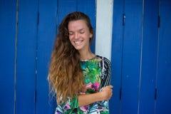 Ciérrese encima de la belleza atractiva con el pelo largo moreno mullido, la sonrisa que está pasando alegre tiempo en una pared  Foto de archivo