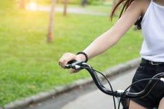 Ciérrese encima de la bici del freno de mano, bicicleta del montar a caballo de la mujer joven en parque foto de archivo