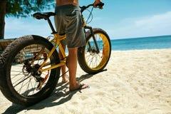 Ciérrese encima de la bicicleta de la arena del montar a caballo del hombre en la playa Deporte del verano Fotos de archivo