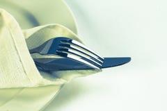 Ciérrese encima de la bifurcación y del cuchillo dinning de los cubiertos con el plato encendido Foto de archivo