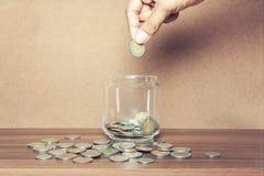 Ciérrese encima de la botella de cristal con la mano que apila las monedas de plata Fotos de archivo libres de regalías