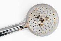 Ciérrese encima de la cabezal de ducha con la cal en ella y colocada en la superficie blanca del fondo foto de archivo